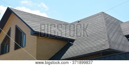 A Close-up On A Roof Problem Area Covered With Asphalt Roof Shingles And Irregular Shape Window On T