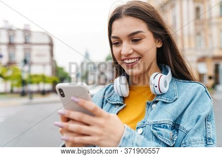 Image of charming cheerful woman with wireless headphones using mobile phone on city street