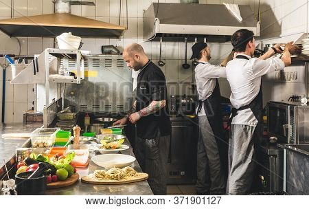 Professional Chef Cooking In The Kitchen Restaurant At The Hotel, Preparing Dinner. A Cook In An Apr