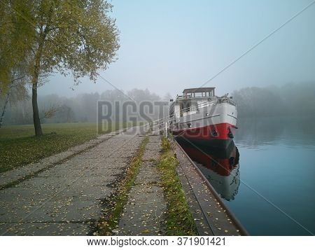 A Ship In A Lonely Harbour At A Foggy Autumn Day In A Serene Scenery With Misty Background And Roman