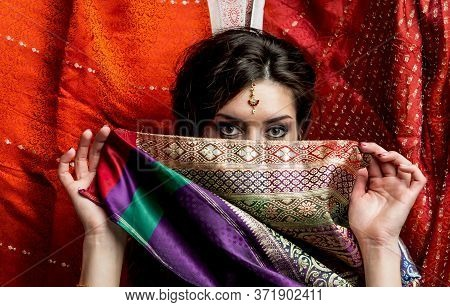 The Young Dark-haired Woman Hides A Face Behind A Piece Of Colorful Indian Saris. Indian Style.