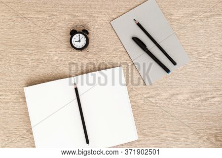 Desktop For Student Or Freelancer. Working Space With Open Notebook, Black Clock For Control Time. W
