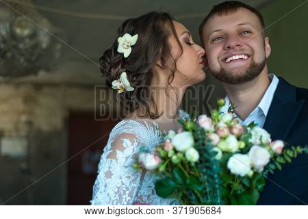 Portrait Of Happy Bride And Groom. Bride Kisses The Groom. Smiling Young People Of Twenty-five Years