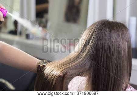 The Hairdresser Uses Hair Spray, Spraying On Flawless Hair. In The Beauty Salon. Beauty And Health H