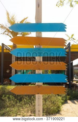 Direction Signs On A Wooden Post. Several Wooden Signs Of Direction Indicators, Place For Text, Copy