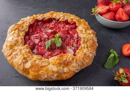 Homemade Summer Flan Pie With Strawberries, Mint And Almond Petals On Dark Background. Selective Foc