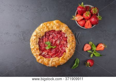 Homemade Summer Flan Pie With Strawberries. Mint And Almond Petals On Dark Background. Top View With