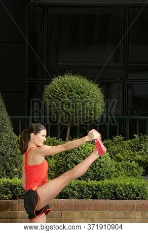 Woman stretching in landscaped garden side view