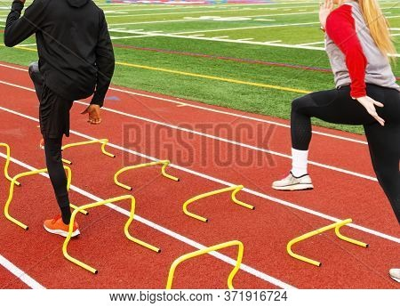 Rear View Of Male And A Female Athletes Running Over Yellow Mini Hurdles Set Up In Lanes On A Red Tr