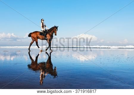 Young Beautiful Woman Ride On Sand Beach. Horse With Rider Run Along Sea Surf By Water Pool. Horseba