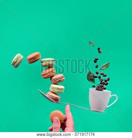 Perfect Balance Concept. Balancing Cup Of Coffee And Macaronos On Index Finger. Creative Square Food