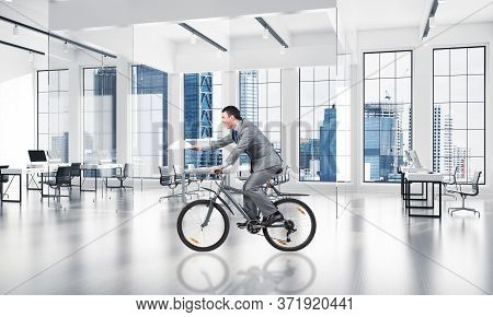 Businessman With Paper Documents In Hand On Bike. Accountant In Business Suit Riding Bicycle At Conf