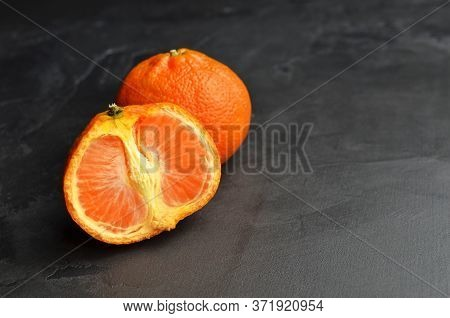 Orange Tangerine Citrus Fruits On Black Background. Tangerine Cut In Half. Copy Space.