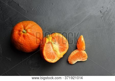 Orange Tangerine Citrus Fruits On Black Background. Tangerine Parts. Top View, Copy Space.