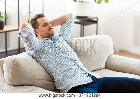 Weekend. Calm Handsome Man Resting At Home On Sofa, Leaning Back With Closed Eyes, Copyspace