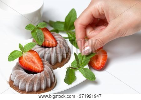Chocolate Fudge Garnished With Half A Strawberry With Petals. Woman Decorates Dessert With Mint And