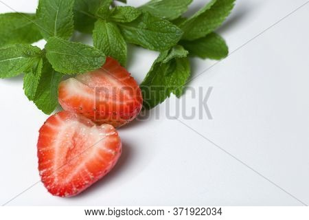 Slices Of Cut Strawberries And Sprigs Of Mint. On A White Surface.