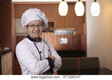 Portrait Of Happy Proud Asian Chef Smiling At Camera With Crossed Arms, Chef In Kitchen, Successful