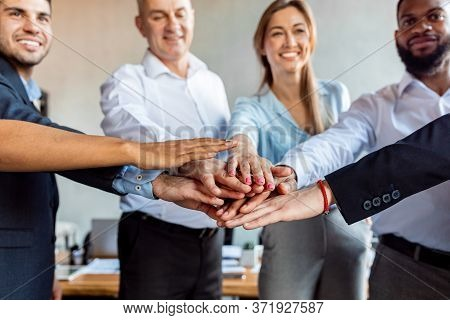 United Coworkers Holding Hands Celebrating Business Success During Teambuilding Event In Modern Offi