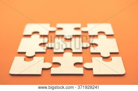 Practically Folded Picture Of Puzzles.close-up Puzzles Lying On An Orange Background. Soft Focus On