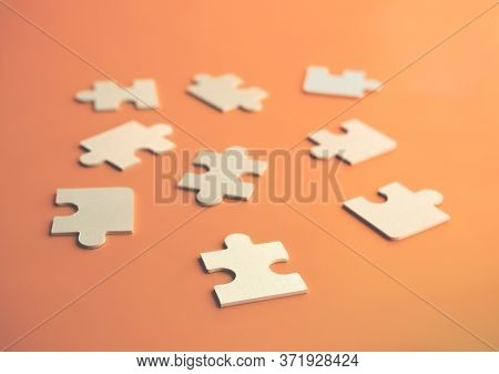 Close-up Puzzles Lying On An Orange Background. A Concept Of Large Wooden Puzzles. Soft Focus On The