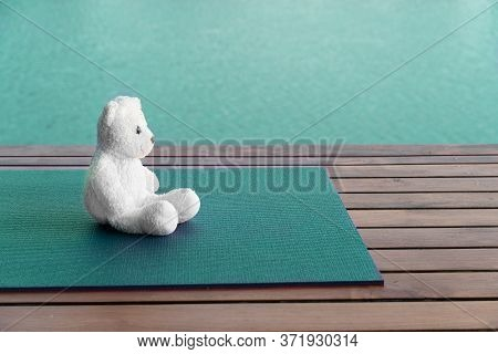 White Fluffy Bear On Blue Green Yoga Map At Wood Terrace With Water Lake Nature In Well Being Or Hea