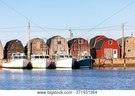 A line of Oyster barns and fishing boats at Malpeque Harbour on the north shore of Prince Edward Island, (PEI) , Canada