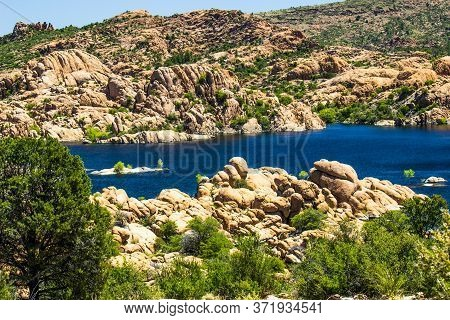 Blue Waters Of Mountain Lake With Unusual Rock Formation Shoreline