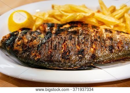 Fresh grilled sea bass served with fried potatoes in white plate