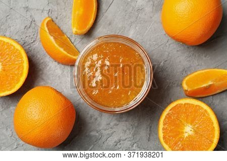 Oranges And Glass Jar With Jam On Gray Background, Top View