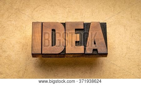 idea word abstract in vintage letterpress wood type against textured handmade paper, business, education or science concept