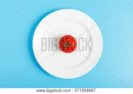 One Red Tomato On A White Plate On A Blue Background. The Concept Of Diet And Refusal Of Food. Conce