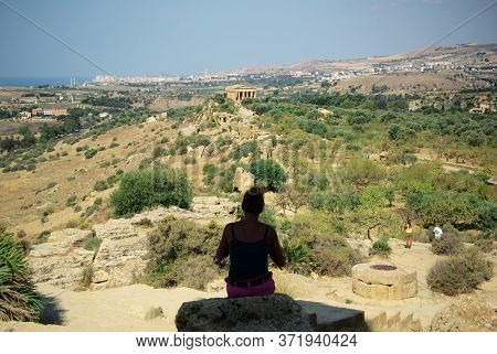 tourist looking at temple of Concordia in the Valley of Temples in Agrigento a  landmark of Sicily tourism and Unesco architecture