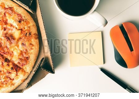 Pizza In Box, Cup Of Coffee, Laptop, Computer Mouse, Pen And Empty Sticker With Copy Space On Desk I