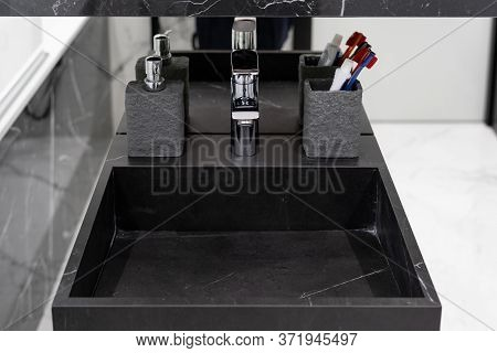 High Angle View Of Silver Water Tap Over Black Marble Sink, Soap Dispenser And Toothbrush, Toothpast
