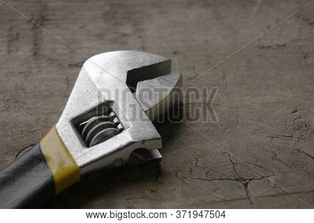 Adjustable Wrench With Yellow Handle On The Wood Background. Minimalist Photo Of Adjustable Wrench W