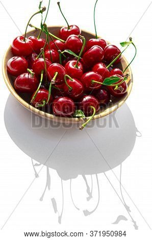The Red Ripe Cherry Rests On A Wooden Plate On A White Background With Sharp Shadows