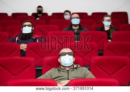 People in cinema with protection mask keeping distance away to avoid physical contact.Coronavirus COVID-19 disease protection.Social distancing practice