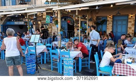 Chania, Crete - June 22, 2019: People At A Greek Restaurant, Chania, Crete. Chairs And Tables In Blu