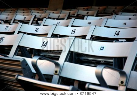 Chairs at a stadium await visitors for the big game poster