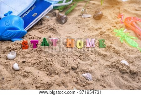 Beach Sand, Shells, Summer, And Words In Wood Letters Stay At Home.