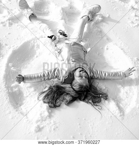 Smiling Child Lying On Snow With Copy Space. Funny Kid Making Snow Angel. Child Girl Playing And Mak