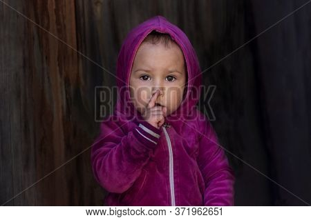 A Little Girl Holds A Finger Near Her Lips And Shows A Gesture Of Silence. A Small Child With A Worr