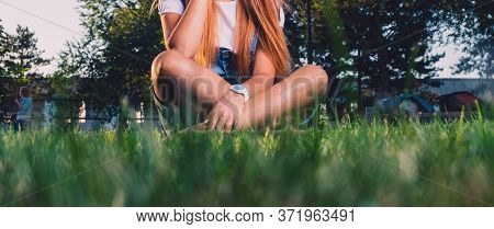 Teen Girl Is Sitting Cross-legged On Grass Worms Eye View