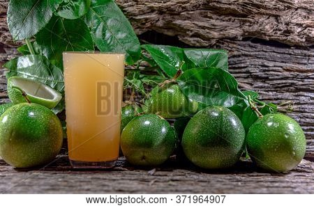 Cocktail And Passion Fruit Juice (passiflora Edulis Sims) And Fresh Green Fruits On A Woody Backgrou