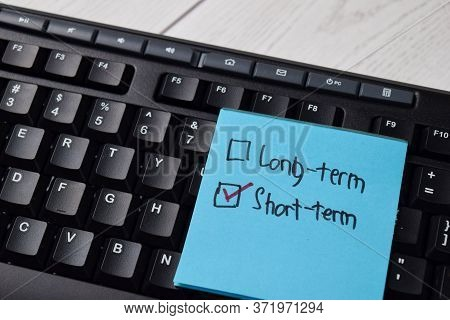 Long-term And Short-term Write On A Sticky Note. Supported By An Additional Services Isolated Wooden