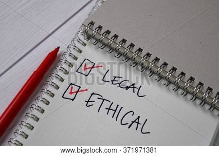 Legal And Ethical Write On A Sticky Note. Supported By An Additional Services Isolated Wooden Table.