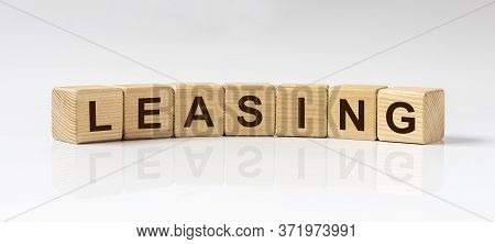 Leasing Word Inscription Written In Wooden Cube Isolated On White Glossy Background With Reflection.