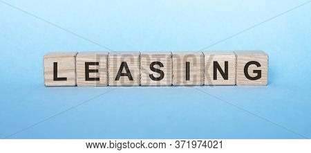 Leasing Word Inscription Written In Wooden Cube Isolated On Blue Background. Leasing Concept