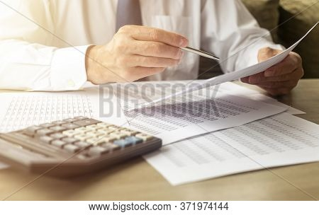 Businessman Analyzing Accounting Financial Documents With Calculator On Wooden Desk In Office. Man H